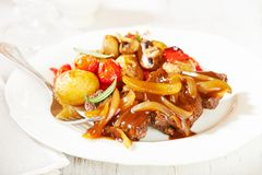 Braised beef with onion sauce and oven baked vegetables royalty free stock photography
