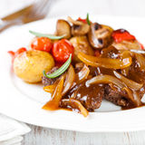 Braised beef with onion sauce and vegetables Stock Image