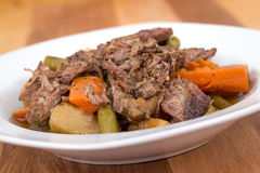 Braised beef pot roast stew. With vegetables on table Royalty Free Stock Image