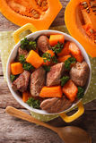Braised beef with pumpkin closeup in the pan. Vertical top view Royalty Free Stock Photography