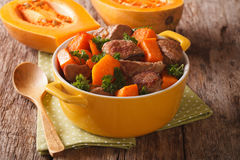 Braised beef with pumpkin, onion and spices close up in a yellow Stock Images