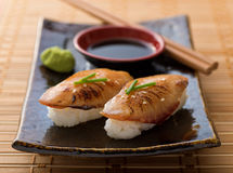 Braised Eel Nigiri. A delicious braised eel nigiri-zushi with wasabi paste and japanese soy garnished with green onion and sesame seeds Stock Photos