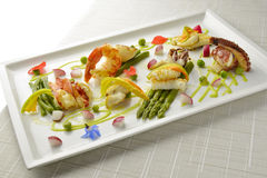 Braised Fish Dish Shrimp Lobster Scallop Squid Octopus Asparagus. Pea Beans in square plate Royalty Free Stock Photography
