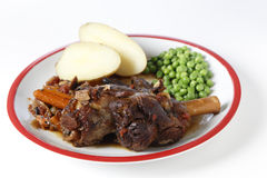 Braised lamb shanks with potatoes and peas Royalty Free Stock Images