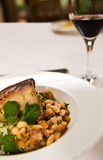 Braised Pork Belly. A peice of pork belly served with beans ang a glass of red wine. Restaurant food Royalty Free Stock Image