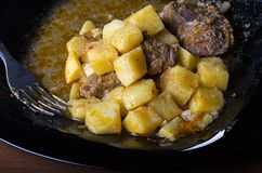 Braised potatoes with meat and gravy on a black plate, closeup 45 view royalty free stock photos