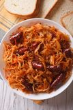 Braised sauerkraut with sausages closeup vertical top view Royalty Free Stock Photo