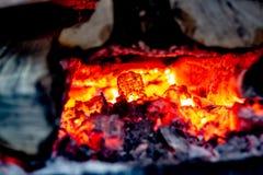 Braises brûlantes dans un fourneau en bois de pays photos stock