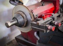 Brake lathe tool polishing disc brakes of cars working. Automatic stock images