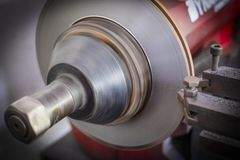 Brake lathe tool polishing disc brakes of cars working. Automatic royalty free stock photos