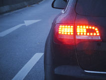 Brake light and arrow. Bright brake lights of car at dusk Stock Photography