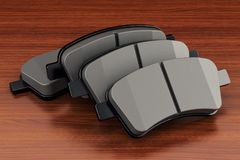 Brake pads on the wooden table. 3D royalty free illustration