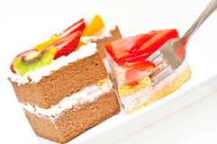 Braking off a pieces of cake with a fork. Against white background Stock Images