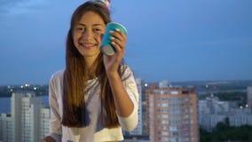 brakits的美丽的长发女孩在吹在一声不同的口哨的一个欢乐盖帽采取从一纸杯的一个饮者 股票录像