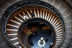 Vatican - February 24, 2016: People going down the spiral stais inside the Vatican Museums. Bramante Staircase is the name given to two staircases in the Royalty Free Stock Image