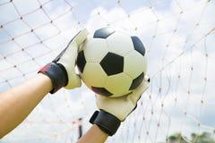 Bramkarz używać ręki dla chwytów piłka obraz stock