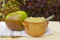 Bramley apple and a pot of apple sauce. Bramley apple and a pot of sweet sauce made of bramley apples on a kitchen cloth. Bramley apple sauce is a traditional stock photos