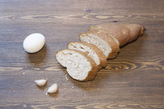 Bran bread, eggs and garlic. On a wooden table royalty free stock photos