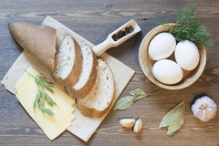 Bran bread, eggs and garlic. On a wooden table royalty free stock image