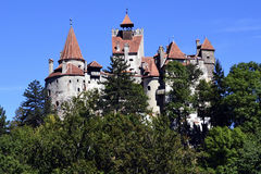 Bran Castle of Dracula - landmark of Transylvania. The castle of Bran, home of Count Dracula, towering over the forested mountain - viewed on a sunny day. A stock images