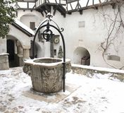 The Bran Castle - snowy fountain in the courtyard Stock Photo