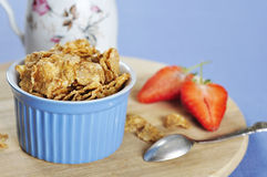Bran flakes cereal  with strawberry. Delicious and nutritious bran flakes cereal in blue bowl with strawberry on wooden cutting board Stock Images