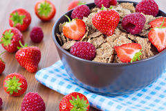 Bran flakes with fresh raspberries and strawberries. On blue checkered cloth. Healthy eating choice concept Stock Image