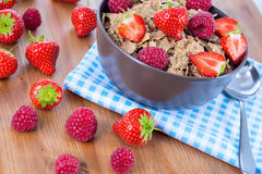 Bran flakes with fresh raspberries and strawberries. On blue checkered cloth. Healthy eating choice concept Stock Photos