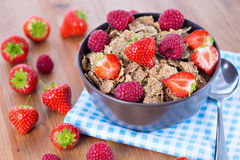 Bran flakes with fresh raspberries and strawberries. On blue checkered cloth. Healthy eating choice concept Royalty Free Stock Photo