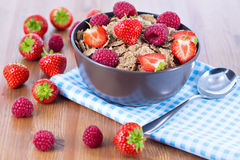 Bran flakes with fresh raspberries and strawberries. On blue checkered cloth. Healthy eating choice concept Royalty Free Stock Image