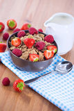 Bran flakes with fresh raspberries and strawberries and pitcher. Bran flakes with fresh raspberries and strawberries on blue checkered cloth and a pitcher of Royalty Free Stock Images