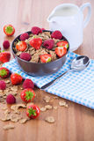 Bran flakes with fresh raspberries and strawberries and pitcher. Bran flakes with fresh raspberries and strawberries on blue checkered cloth and a pitcher of Royalty Free Stock Photography