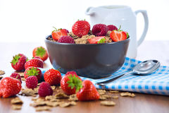 Bran flakes with fresh raspberries and strawberries and pitcher Royalty Free Stock Images