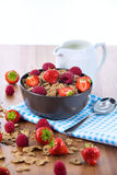 Bran flakes with fresh raspberries and strawberries and pitcher. Bran flakes with fresh raspberries and strawberries on blue checkered cloth and a pitcher of Royalty Free Stock Image