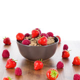 Bran flakes with fresh raspberries and strawberries. On wooden table. Healthy eating choice concept Royalty Free Stock Photos