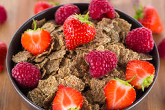 Bran flakes with fresh raspberries and strawberries. On wooden table. Healthy eating choice concept Stock Image