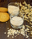 Bran and flour oat in glass with cookies on board Royalty Free Stock Image