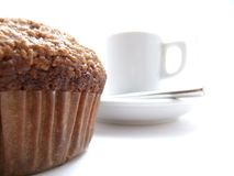 Bran muffin and coffee. Bran muffin in foreground and white espresso coffee cup in the background Stock Photos
