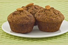Bran muffins. Healthy bran muffins with almonds on white plate and pale green placemat Stock Photo