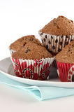Bran muffins. In decorative cups on white background in vertical format Royalty Free Stock Images