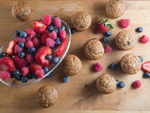 Bran muffins and berry fruit on wooden board Royalty Free Stock Photography