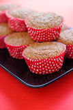 Bran muffins in bright red and white paper holders on a black rectangular plate and. Red background Royalty Free Stock Images