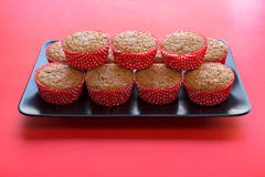 Bran muffins in bright red and white paper holders on a black rectangular plate and. Red background Royalty Free Stock Photography