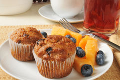 Bran muffins with fruit. A plate of bran muffins with cantaloupe and blueberries Stock Images