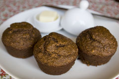 Bran muffins on plate. Three bran muffins set on plate with butter Royalty Free Stock Image