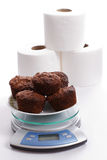 Bran Muffins and Toilet Paper. A plate of bran muffins on a kitchen scale with 3 rolls of toilet paper Royalty Free Stock Photography