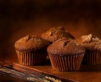 Bran muffins. On a wooden board with some wheat in the froont stock photography