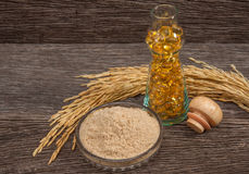 Bran oil capsule in bottle glass. With seed and bran on the old plank wood Stock Photo