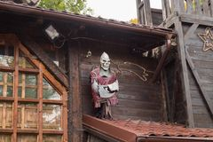 Decorative figure of death with an ax attached to the wall near the entrance to the Bran castle in Bran city in Romania royalty free stock photo