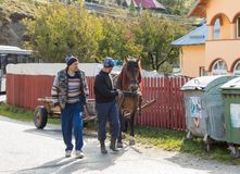 Two men lead by the bridle of a horse harnessed to a wagon in a suburb of Bran city in Romania. Bran, Romania, October 09, 2017 : Two men lead by the bridle of a Royalty Free Stock Photos
